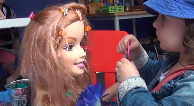 Dziewczynka czesze głowę lalki
