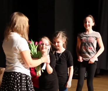 Grupka młodych artystek z kwiatami i dyplomem
