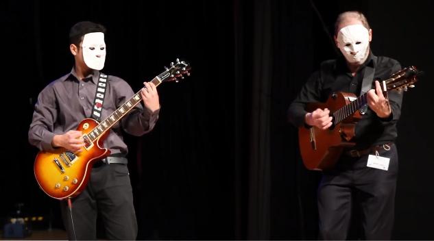 2 aktorów w białych maskach grających na gitarza