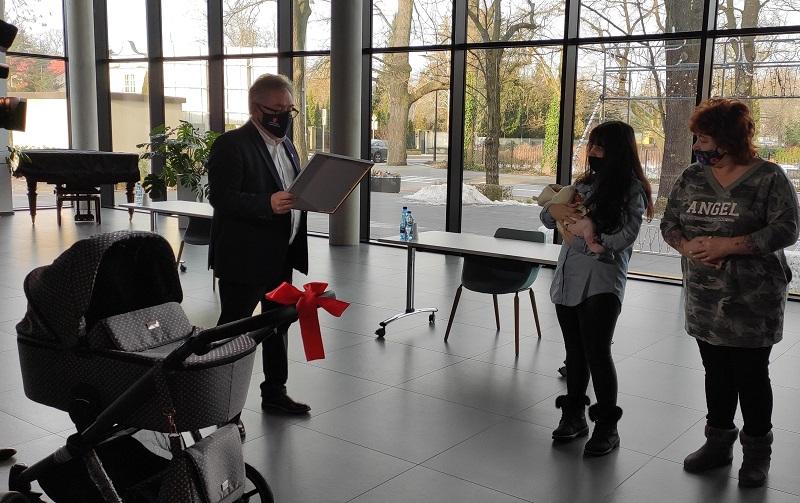 Burmistrz wręcza dyplom dla noworocznego dziecka oraz wózek