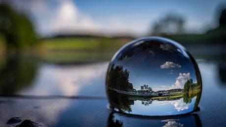 Jeziorko otoczone zielenią, w wodzie szklana kula z odbiciem jeziora