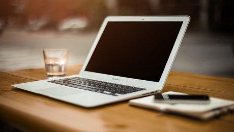 Laptop, szklanka wody i notatnik